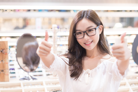 beauty woman wear eyeglasses and show thumb up in the store Stock Photo