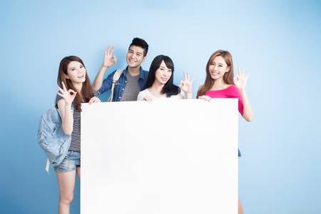 happy group student take billboard and show ok on the blue background
