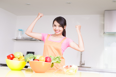 beauty housewife show fist and smile in the kitchen photo