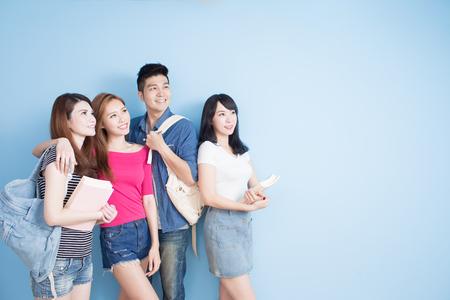 青色の背景のどこかに幸せなグループ学生見て