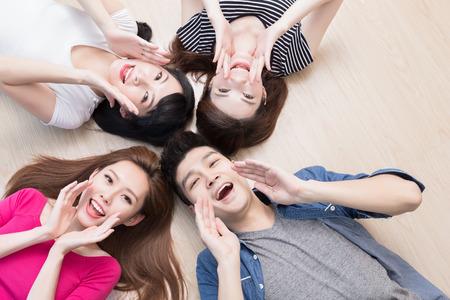 I giovani sorridono felicemente e distesi sul pavimento Archivio Fotografico - 83944450