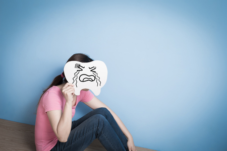 woman take cry tooth on blue background Stock Photo
