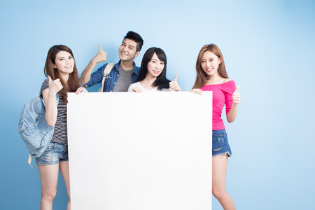 happy group student take billboard and shoe thumb up on the blue background photo