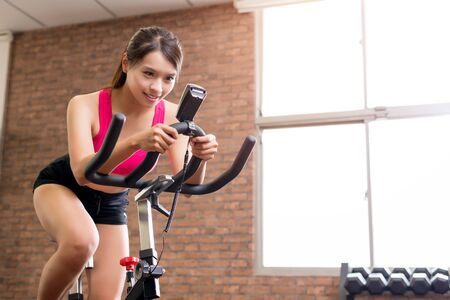 woman smile happily and use exercise bike photo