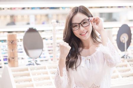 아름다움 여자는 안경을 쓰고 가게에서 주먹을 보여줍니다.