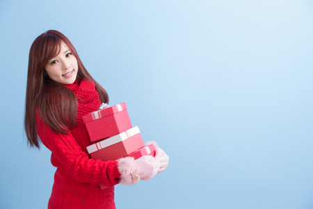beauty woman take gift and smile to you in christmas isolated on blue background, asian