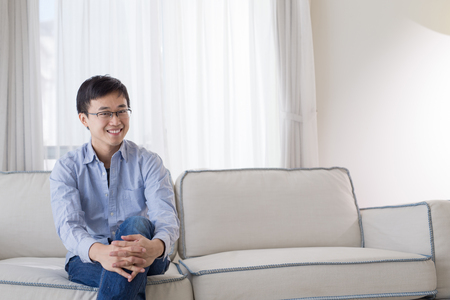 comfortable: man smile happily and sit on sofa at home