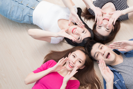 젊은 사람들이 행복하게 미소 짓고 바닥에 누워있다.
