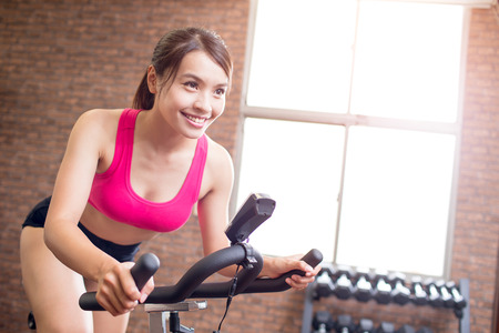 woman smile happily and use exercise bike Stock Photo