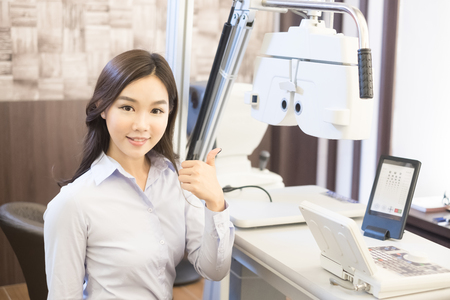 woman smile and thumb up with optometry in the optical shop