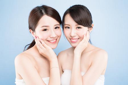 파란색 배경에 건강한 피부 관리와 두 아름다움 여자
