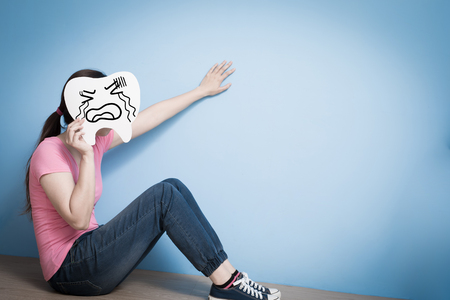 display problem: woman take cry tooth on blue background Stock Photo