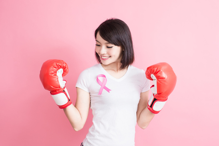 woman take glove with chest health concept on the pink background