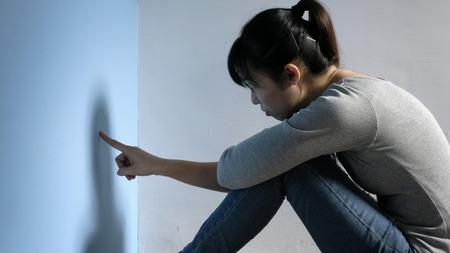 De depressie vrouw zit op de vloer