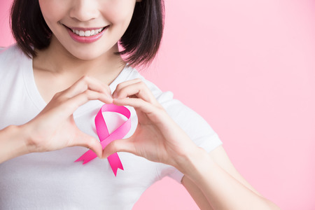 woman show heart to you with chest health concept on the pink background Stock Photo