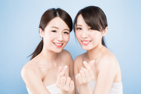 二つの美しさの女性は青い背景に健康なスキンケアと心のジェスチャーを表示します