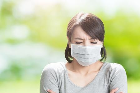 여자는 아프고 녹색 배경에 추위를 느낍니다.