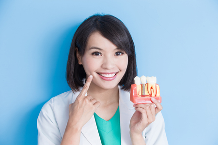 woman dentist take implant tooth and touch her face on the blue background