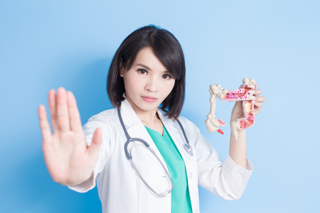 beauty woman doctor show stop to you with colorectal cancer concept on the blue background