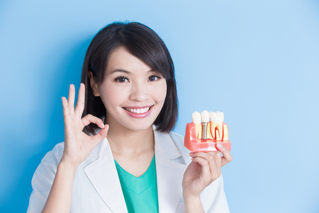 woman dentist take implant tooth and show ok to you on the blue background