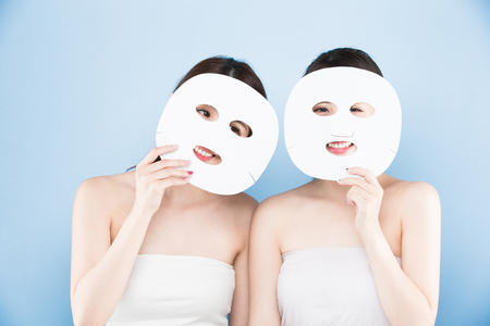 two beauty woman take mask with make up concept on the blue background