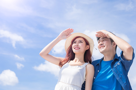couple wear sunglass and look somewhere with sky