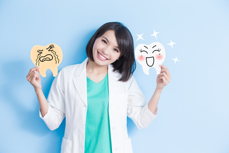 여자 치과 의사 걸릴 부패와 파란색 배경에 건강 치아 보드