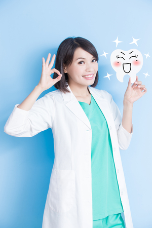 woman dentist take tooth board and show ok to you on the blue background Stock Photo