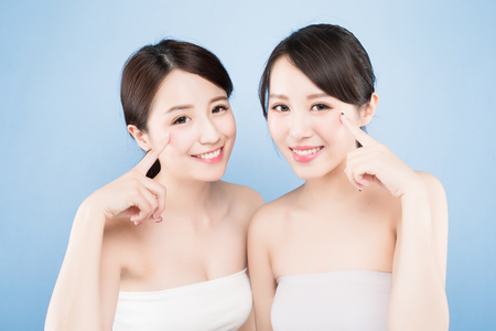 salon background: two beauty woman pointing her eye with healthy skin care on the blue background