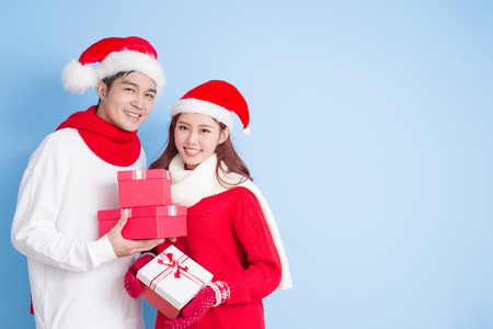 couple feel confuse and take present with merry christmas on blue background