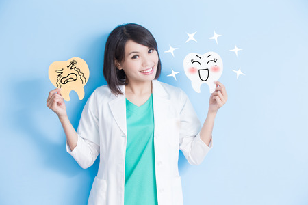 woman dentist take decay and health tooth board on the blue background Stock Photo