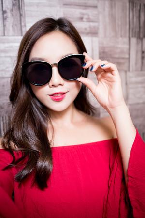 sexy asian woman: beauty fashion women wear sunglass on the wall