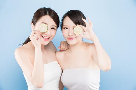 twee schoonheid vrouw nemen citroen met make-up concept op de blauwe achtergrond
