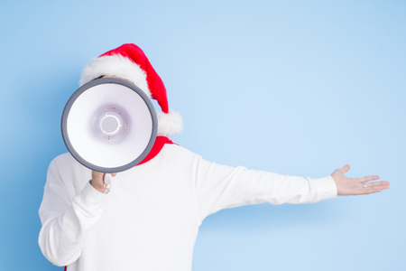 man take microphone and show something with merry christmas on the blue background