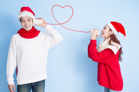 couple smile and use can phone with merry christmas on the blue background