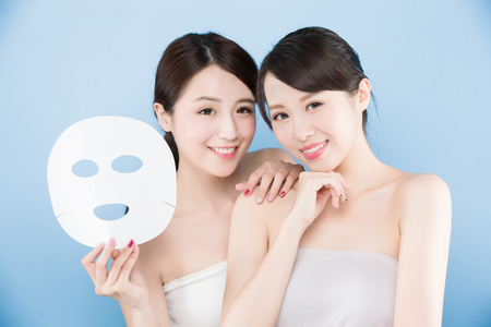 two beauty woman take mask with make up concept on the blue background 免版税图像 - 90767341