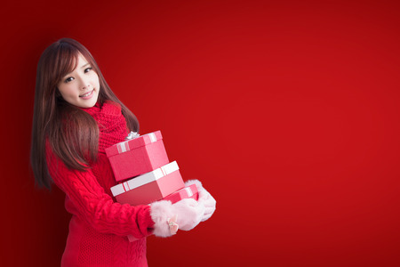 beauty woman take gift and smile to you with christmas on red background 版權商用圖片