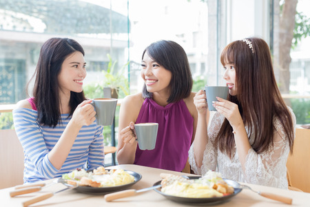 happy woman friends sitting and chatting in restaurant