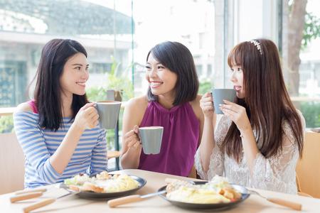 amis de femme heureuse assis et bavarder dans le restaurant