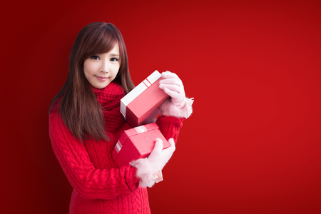beauty woman take gift and smile to you with christmas on red background Stock Photo
