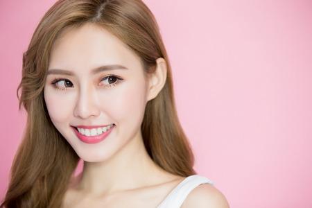 美容スキンケア女性はピンクの背景のどこかに見える 写真素材