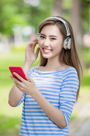 女性は幸せに微笑み、電話を使用して公園で音楽を聴きます
