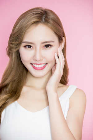 beauty skincare woman touch her face on the pink background