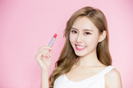美容スキンケア女性はピンクの背景に口紅を取る