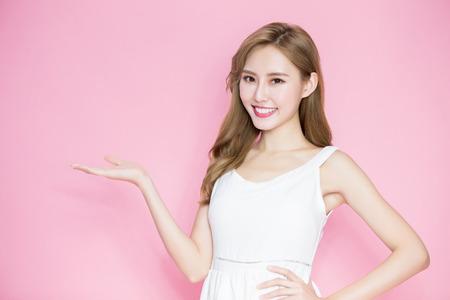 schoonheid huidverzorging vrouw iets laten zien op de roze achtergrond