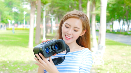 beauty woman use VR happily in the park