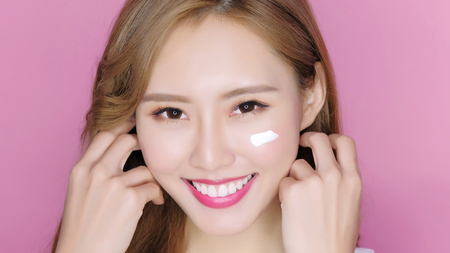 beauty makeup woman smile and applying moisturizer cream on her pretty face Stock Photo