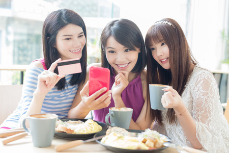 happy woman friends take phone and credit card in restaurant