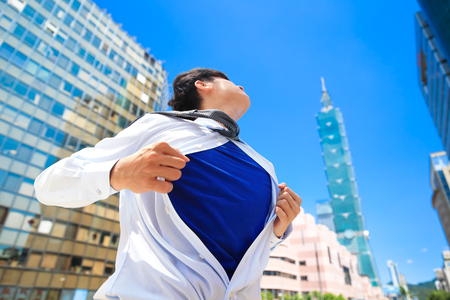 Business man pulling his t-shirt open and showing a superhero suit underneath suit in the taipei Stock Photo