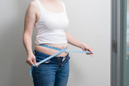 Fett Übergewicht Frau nehmen Taille Lineal mit grauem Hintergrund Standard-Bild - 91511167